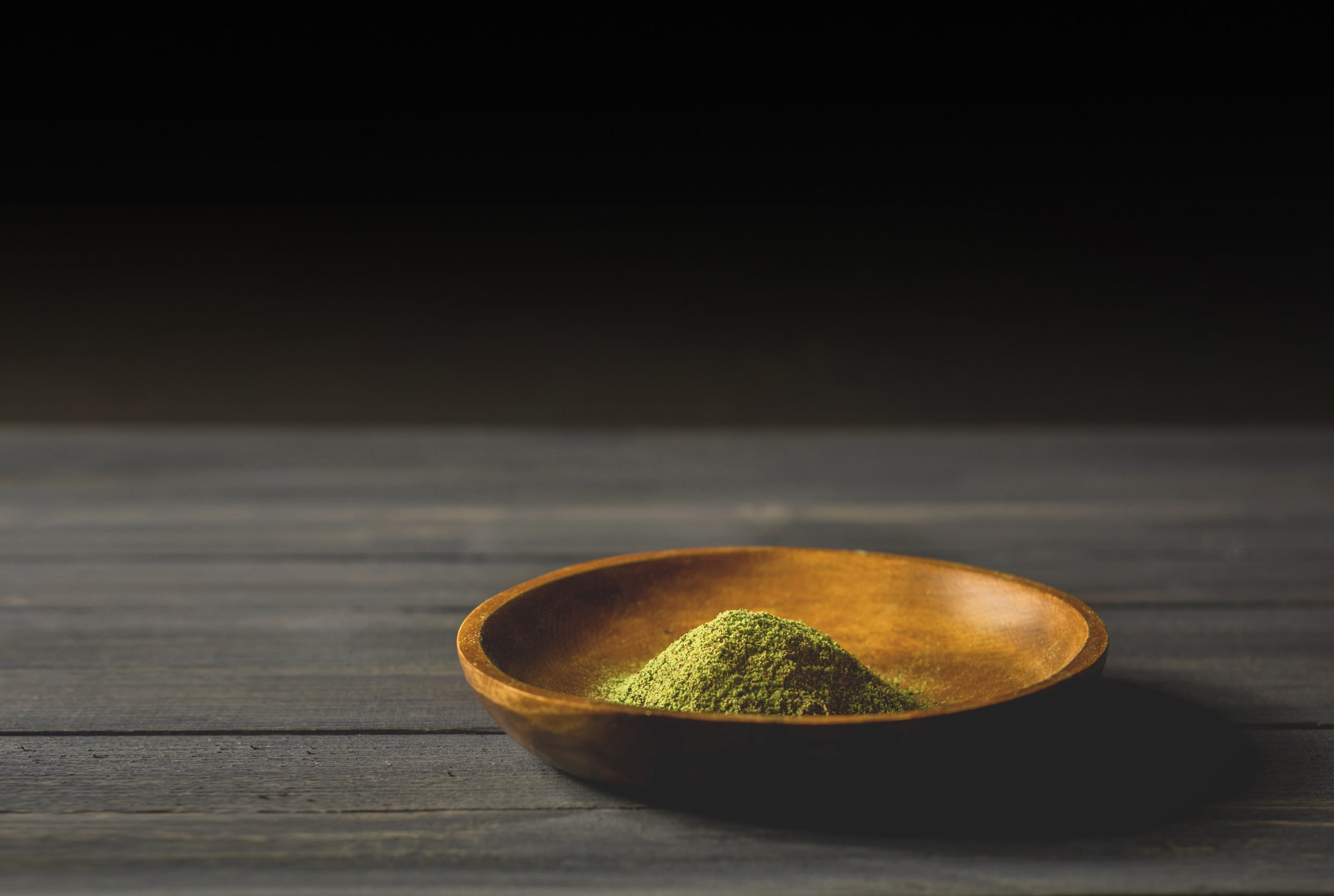 Mitragynina speciosa or Kratom powder in wooden bowl on table, chiaroscuro effect
